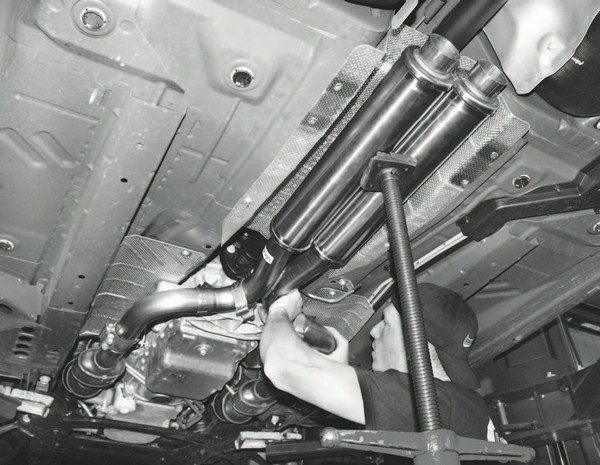 Because this project car had an automatic transmission and GM's cylinderdeactivating Active Fuel Management feature, the exhaust system included a pair of additional resonators that aren't part of the kit for manualtransmission cars. The resonators are necessary to accommodate the four-cylinder exhaust note when half of the cylinders temporarily shut down. Note, too, how a transmission jack is used to hold the resonators in the correct position while they're being bolted to the converter flow tubes.