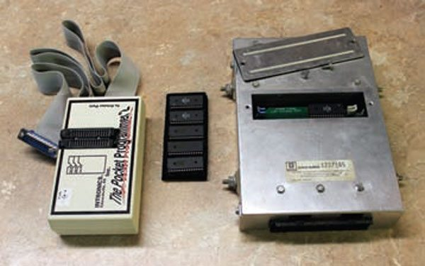 The 1986–1989 TPI ECM (right) contains a PROM carrier (called a MEMCAL) that is installed inside the ECM case. This MEMCAL adapter (beneath the removed ECM cover) bypasses the PROM soldered to its carrier so that a flash PROM can be removed. This equipment requires the removal of the flash PROM for every update made to the engine calibration. The PROM is then inserted into a programming device (left) for erasing and reprogramming. It is a tedious process that many tuners avoid today, making OBD-I tuning a service no longer offered by many engine tuners.