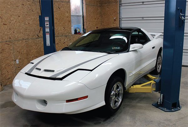 This 1997 Trans Am has been previously modified with a 383-ci LT1 engine and Pacesetter long-tube headers. Here, the car is loaded on the lift to prepare for the 24x LT1 installation.