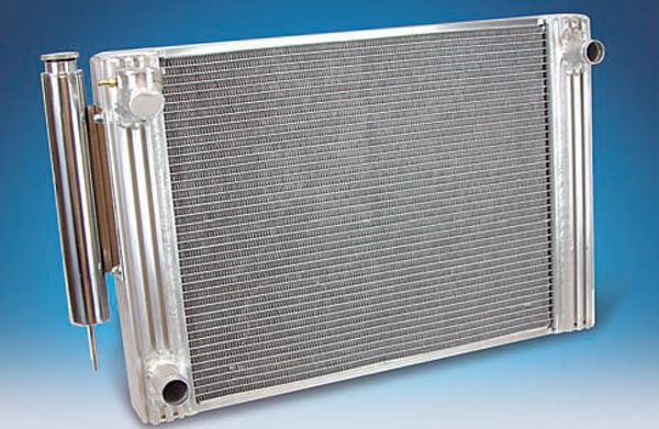 This Flex-a-lite aluminum radiator features a built-in overflow canister. Having a custom crossover radiator built with the inlet and outlet on both sides gives you a lot of hose-routing options during an LS swap. However, in some cases the expense is prohibitive. Since most LS engines do not use mechanical fans, routing a hose across the front of the engine is not an issue. (Photo Courtesy Flex-a-lite)