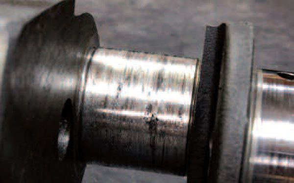 Many crankshafts will exhibit little, if any, visible wear on the journals. However, wear can be significant on cranks with a lot of miles or from an engine with a poor maintenance record. This one is particularly bad off as it even has bearing material embedded in it. This crank could still be salvageable; even though GM does not recommend grinding its cranks, many engine machinists will tell you this is baloney. You'll need to have a machine shop take a look at a crank like this to determine whether it's toast.