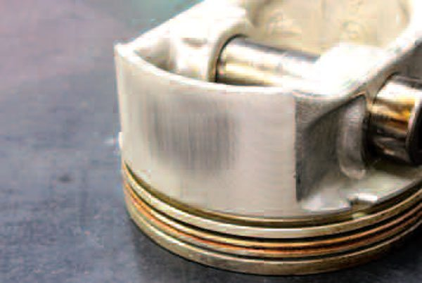 A stock piston may very well be in good shape, exhibiting little wear or even carbon buildup. Conversely, check out the wear markings on this 42,000-mile Gen III piston. Skirt scuffing like this is one of the reasons that GM switched to polymer coated skirts for all Gen IV engines (as well as on stock replacement Gen III pistons—but this coating gets scratched and wears off over time, too). But no matter its visible condition, a piston is one engine part you do not want to reuse.
