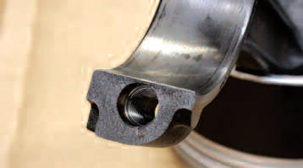 Gen III/IV connecting rods use bolts that thread into the beam end of the rod to hold the caps in place. (Prior small-blocks normally used press-in studs with nuts that held the cap.) Inspect these threads for obvious imperfections. Since this is a highly stressed area, any thread damage will probably render the rod unusable (so says GM), but check with your machine shop if you're unsure.