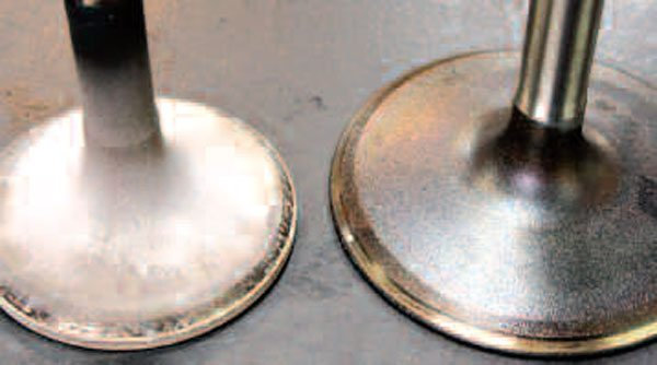 These LS1 valves are in decent condition; it's normal for the top of an exhaust valve (left) to be covered in a light-colored soot, as this indicates a clean-burning engine. The area atop an intake valve (right) will have an oily appearance, and engines that have seen a lot of service may also have black carbon buildup here. Though you should have a quick look at your valves for any unusual wear on the stems or seating surfaces, your machine shop will have the final say as to whether they are reusable (see Chapter 5 for more information). Stock replacement as well as high-performance valves (such as larger valves or those made from lightweight titanium) are available from both GM and the aftermarket.