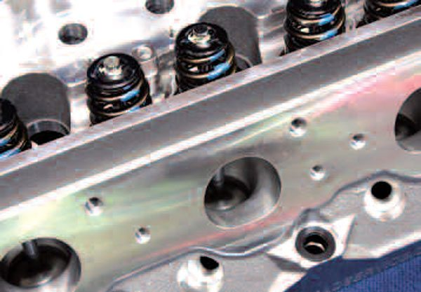 Another great feature of the RHS ProElite head is its raised valve cover rail, which affords more clearance for aftermarket rocker arm systems when using stock valve covers. You can also see that these particular heads are supplied assembled with COMP Beehive valve springs good to 0.600-inch lift, but springs for even higher lifts and solid roller cam setups can be had as well. Also note the steel head bolt hole inserts (bottom right).