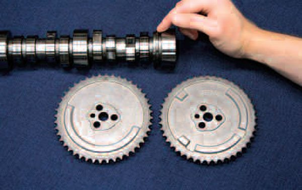This photo notes the important difference between cam sensor placement on Gen III and IV engines. If using a Gen III block's rear-mounted cam sensor, you'll need a cam with a sensing ring located just forward of the rearmost journal (finger pointing). Similarly, if you are using the Gen IV-style cam sensor that mounts in the front cover, your timing chain set's cam sprocket will need one of two types of land-and-groove patterns: the bottom left sprocket is for earlier engine computers needing a 24X crankshaft reluctor ring (and 1X cam sensor signal), while the bottom right shows a sprocket for later engine computers that utilize the 58X crank reluctor and require a 4X cam sensor signal. Keep in mind too that you'll need a specialty sprocket (that can accommodate the required actuator) if you're rebuilding an engine with VVT.