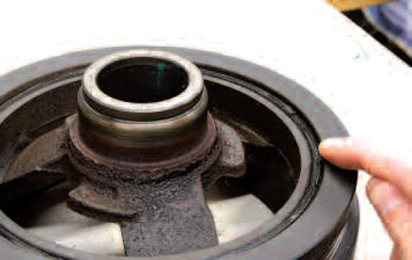 If you'd like to reuse your harmonic damper, have a look at the section of rubber connecting the inner portion of the damper to the outer ring. Any dry-rot or other evidence of poor condition here makes reuse of the damper impossible. Also inspect the surface where the crank seal rides. It's possible to buy a sleeve to repair this area if needed, but chances are that if this surface is sufficiently worn, the unit's damping function probably isn't too well off anymore, either.