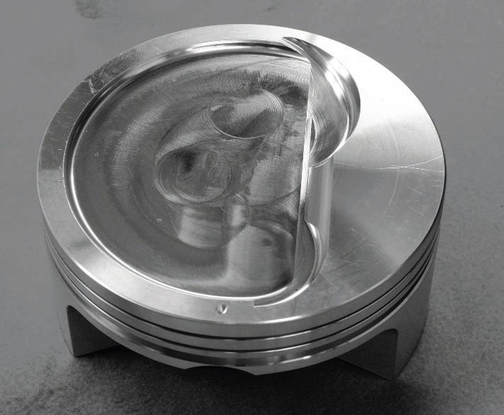 Here's a look at the production, forged-aluminum LS9 piston. Note that it is dished to minimize compression ratio, but that there is also a slight dome within the dish. It helps reflect the incoming air/fuel charge back toward the spark plug for greater combustion efficiency. It also has a unique ring pack that uses relatively thick top and secondary rings and a very thin, minimal bottom oil-control ring. The specialized machining process of the block enables tighter tolerances that, in turn, allows for the thinner, lowerfriction oil-control ring. Also note the friction-reducing Teflon coating on the skirt. In short, the LS9 piston is all about low friction and high rpm. It would make a good choice for low- to moderate-boost engines projected to make about 750 to 800 hp. (Photo courtesy General Motors)