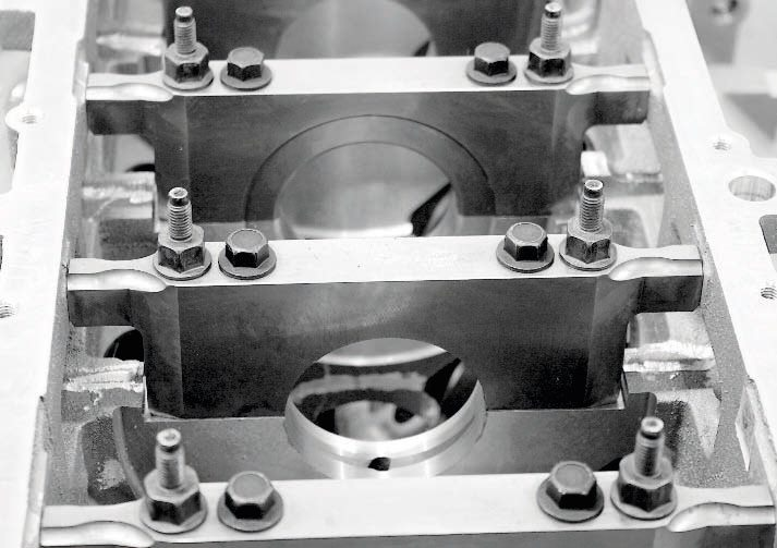 Although the relatively economical LS7 cylinder block is robust enough for low- and mild-boost engines, there are definite product advantages to the more expensive C5R. The main bearing caps are a great example. On the left is the C5R and its racing-bred billet steel main caps and premium ARP studs and fasteners. On the right is the production-based LS7 block's main caps and fasteners; they're still strong pieces, but there's a definite edge with the more expensive C5R.