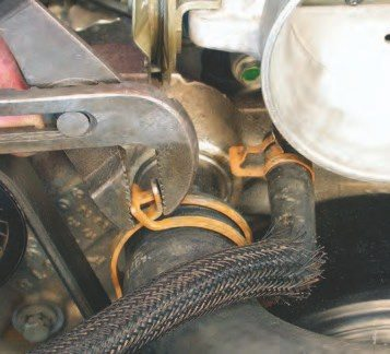 5. Next, remove the upper radiator hoses using pliers to compress the clamps and sliding them back from the radiator mounting tube. These clamps can be reused.
