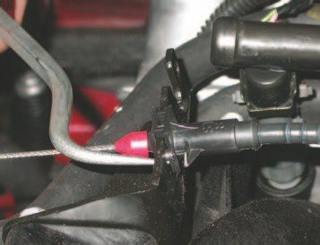 6. To remove the throttle cable, use the radiator hook tool to push on the locking tab through a hole in the bracket towards rear of the vehicle. With the locking tab released, slide the cable anchor up and out of the bracket.