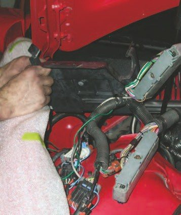 17. Remove the PCM mount (in hands) by taking out the two 10-mm hex-head bolts going into the shock tower sheetmetal.