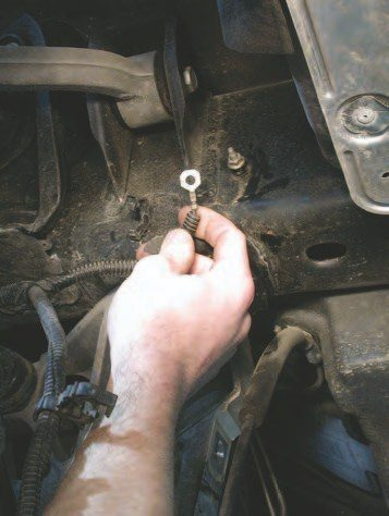 16. Remove the 10-mm hex-head bolt holding the multiple ground wires on the frame on the driver-side of the frame rail at the rear of the vehicle.