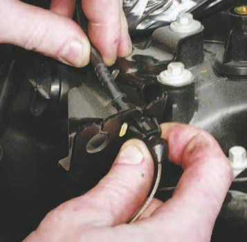 11. Remove the throttle cable by holding the throttle at WOT and unlooping the cable off the throttle blade cam. Depress the two tangs on the anchor of the cable housing to pull it out of the bracket.