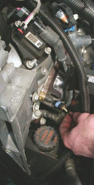 23. Now, pull the water temperature sensor wire connector off the sensor on the driver-side front of the engine block by lifting the lock tab and pulling the connector off.