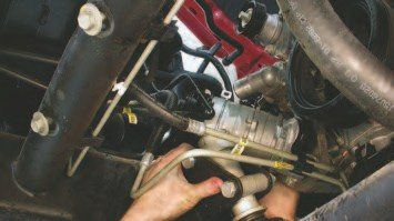34. Perform the same swing-away process on the A/C compressor. First, remove the two 15-mm hex-head bolts on the side of the A/C pump and remove the bottom two 15-mm bolts. Then, push the A/C compressor up and over towards the passenger side of the engine bay to clear the engine. Use wire or zip-ties to hold it out of the way.