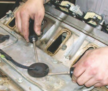 "4. The Gen III V-8 has two knock sensors that bolt to the block deep inside their ""nests"" in the intake valley cover plate. You need to remove the wiring connectors to prevent the wiring harness from being damaged in the process of tearing down the engine. The first step is to gently pry the rubber grommet loose using two screwdrivers, as shown."