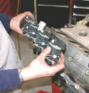 8. Each spark plug on the Gen III has its own coil, with four coils mounted on each valve cover. GM has used two methods to mount the coils to the valve covers. One system, shown here, has the coils mounted on a single bracket. In the other method, used from 1997 to 1998, the coils are mounted separately to the valve cover (these valve covers have perimeter bolts on the valve covers unlike later versions that have the four bolts down the center of the valve cover). To remove the bracket-mounted coils, you'll need to remove the 6-mm diameter bolts with a 8-mm hex-head socket.