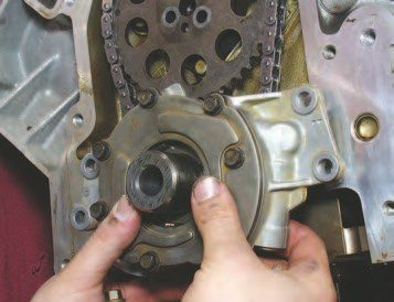 28. Apply a few drops of engine oil to the crank snout and place the bare oil pump body over the snout of the crank (this oil pump will be disassembled in the next step). The four 8-mm fasteners will need a drop or two of blue Loctite on them before they're finally torqued to the 18 ft-lbs, but don't do that yet. To align the pump body to the crank, attach the disassembled pump body on the engine with two fasteners torqued to an initial force of 45 in-lbs. This low torque level will allow you to center the pump body on the crank to avoid uneven wear in the pump.