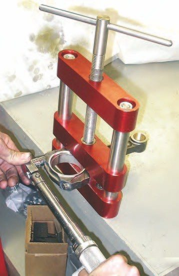 1. You'll need to remove the rod cap in preparation for creating the proper rod bearing clearances. Begin this process by placing the rod in an aluminum rod clamp and using a large breaker bar to loosen the rod bolts. Don't use a standard bench vise for this job as any nick or ding in the rods caused by the vise will become a stress riser that could cause the rod to fail prematurely. The rod clamp is made of soft aluminum and has a wide, flat surface to spread the clamping load out over the rod surface without damaging it.