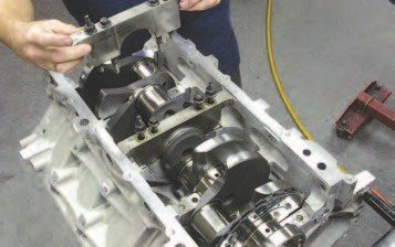 4. Drop the main caps in place on the engine block. Notice how the deepskirted Gen III V-8 engine block allows for main caps with four vertical bolts and two horizontal bolts. The factory main caps are powdered metal and can handle up to 550 hp, while aftermarket billet steel main caps can handle over 650 hp. The factory caps don't have dowels, but many of the aftermarket caps do. The factory caps nest into the sides of the block for an almost swedge-like fit.