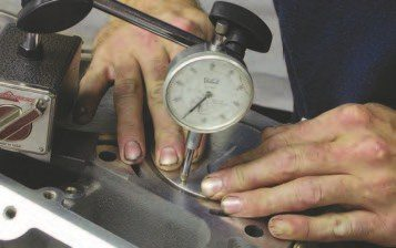 1. Locate the dial indicator on one side of the top of the piston at TDC. With the crank held in place, push on the thrust face of the piston and set the dial indicator at zero.