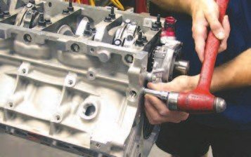 1. The modified factory oil pump has been located and mounted to the front of the crank snout (see Chapter 6 for tips on the factory oil pump locating process). The pressurized oil flows down the side of the engine block in a large main gallery. A welsh plug needs to be installed in the block 2.5-mm deep with a tolerance of +/- 0.3 mm to get the oil to flow down this gallery (shown being installed). When an engine is torn down, this plug is removed to clean the main oil gallery with a brush. Notice the custom W2W billet outlet on the factory pump — this is used to mate up with the internal passage that has been ported to increase oil flow out of the pump and mate up with the custom dry-sump oil pan.