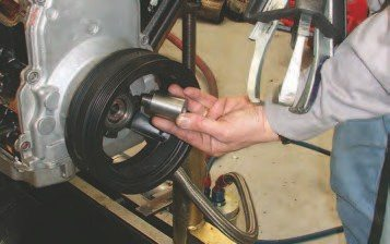 5. To access the camshaft, you'll have to remove the balancer. The crank is threaded for a balancer bolt, so W2W has created this spacer for the balancer puller bolt to seat against to protect the threads. Then remove the water pump. When reinstalling the harmonic balancer, torque it to 37 ftlbs (50 N-m), and then another 140 degrees (which will be tough to do!).