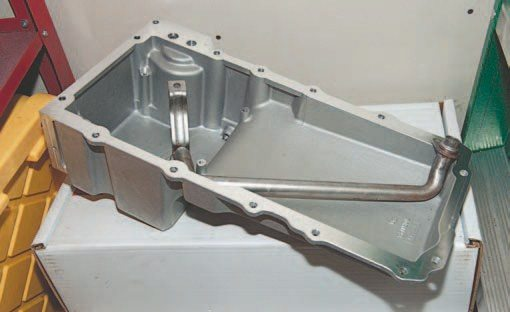 The Holley-machined aluminum LS swap oil pan (PN 302-1) comes with sump baffle, pickup tube, plug, oil passage cover, and oil filter stud. It is designed to work with the stock LS3 dipstick (GM PN 12634547) and tube (GM PN 12625031).