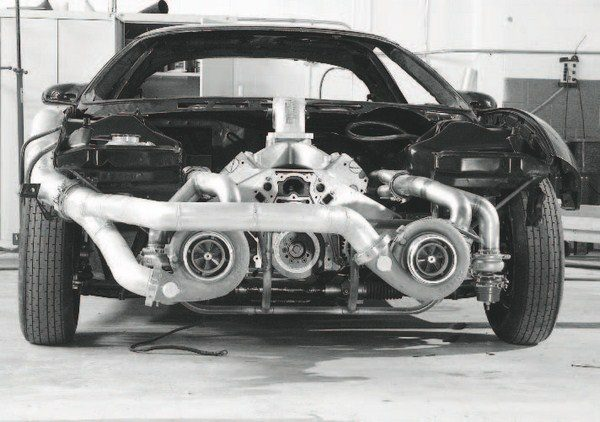 "The advantage of turbocharging in a racing application is clearly illustrated in this partially constructed fourthgeneration Firebird, as two very large turbochargers have been adapted to an LS engine. Except for the older, ""71""-series superchargers used in Top Fuel, Top Alcohol, and some Pro Mod-type drag racing classes, there aren't Roots and screw-type superchargers capable of delivering the airflow of a pair of extra-large turbos. Even large centrifugal blowers are typically limited to only one per engine. With a pair of turbos, each driven by half of the cylinders, the only real limit is keeping the engine itself together under maximum boost."