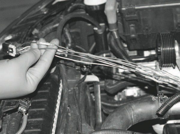 After the individual wires for the throttle-body harness are exposed, they are cut and extension wires are inserted. The Magna Charger kit comes with extension wires matched to the colors of the original harness, making the task simpler. To prevent the joints of the extensions from bundling together in a bulky pack, the original wires were cut at different points for different lengths. This spaces out the joints for a cleaner, more finished product that fits within the protective loom cover.