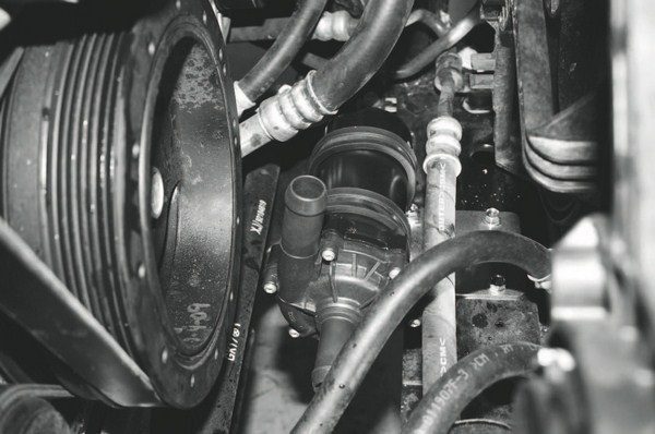 The brake-booster connection finishes off the connections related to the engine, so the final step is the installation of the charge-cooling system components. On the independently circulated liquid-to-air system with the Magna Charger system, installation begins with mounting the system's electrically driven water pump (arrow).