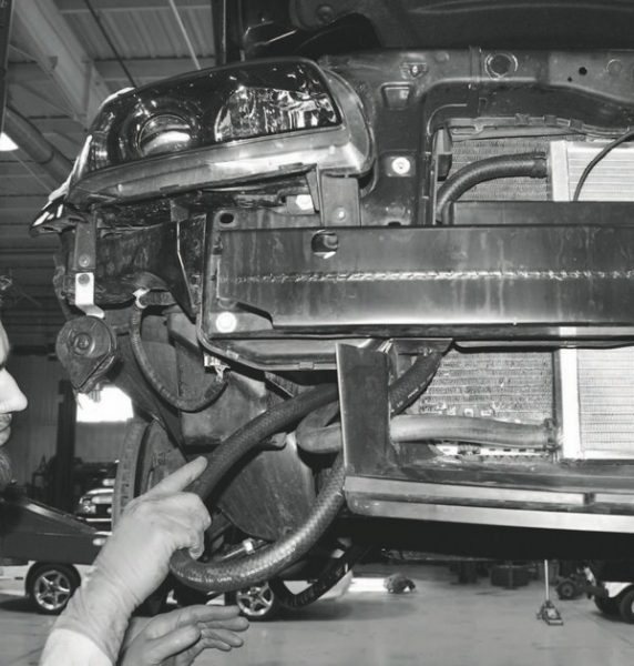 """Next, the coolant hoses are routed to and from the heat exchanger between it, the water pump, and the reservoir tank. Again, routing and placement of the hoses varies among vehicles; and it typically requires the modification or removal of components located behind the vehicle's front fascia. In the case of this G8, it requires creating a passageway through a plastic """"wall"""" located beneath the bumper."""