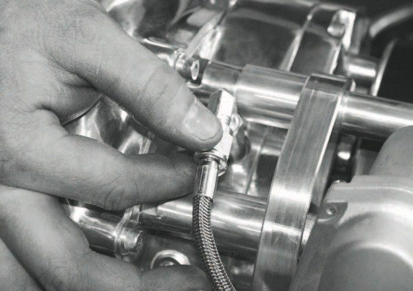 With the supercharger and its mounting-bracket components securely tightened, the oil-feed line from the engine is connected to the compressor.